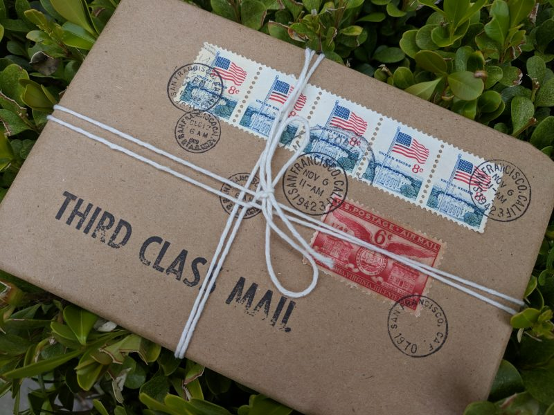 brown paper package tied with string. Postage stamps and postmarks