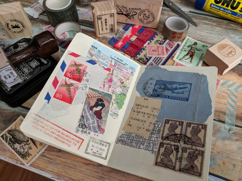 a notebook spread is covered with postage stamps