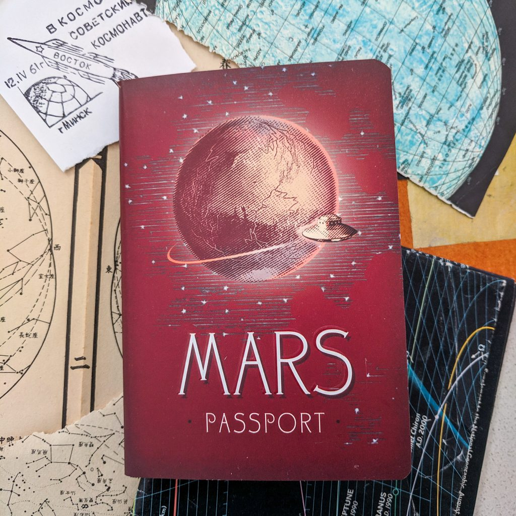 "A ""Mars Passport"" sits atop a stack of space-related papers"