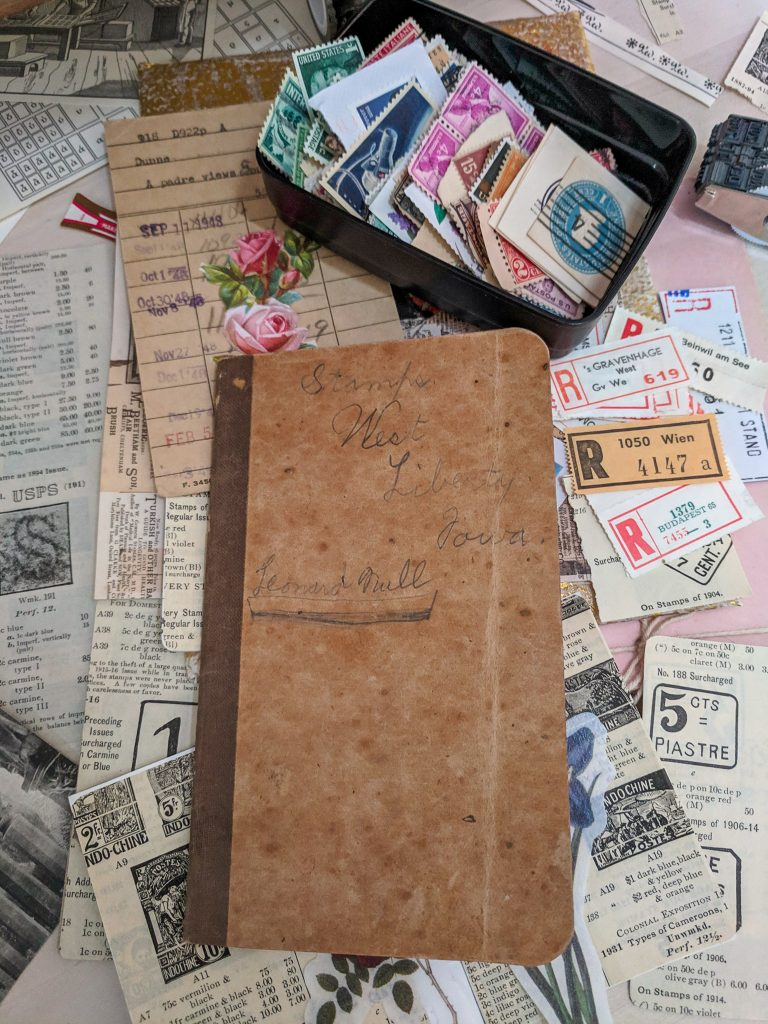 The cover of an old stamp album is displayed, lying on top of a messy desk of collage papers.