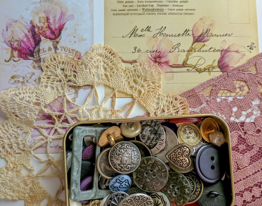 Lace and a doily complement some vintage-inspired papers, along with some vintage buttons