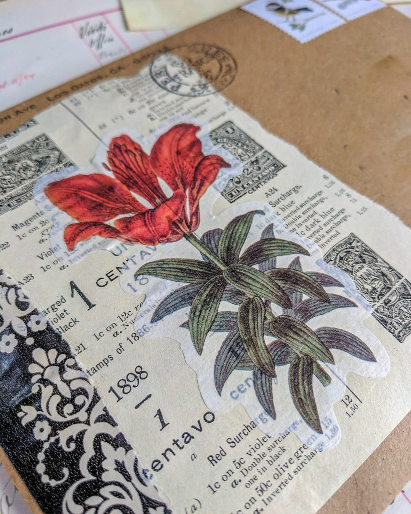 an envelope is decorated with a vintage book page and a floral image