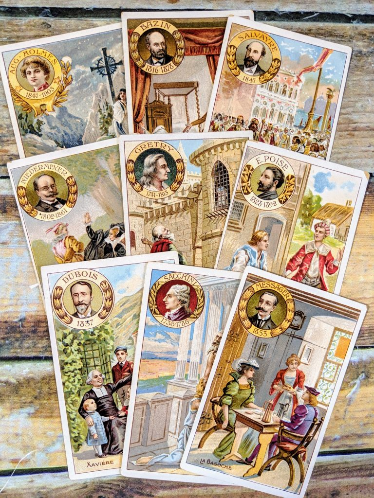 A set of 9 vintage trade cards laid out on a table