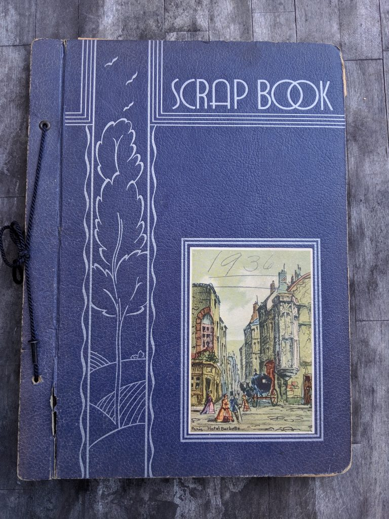 "A blue cover with the word ""Scrap book"". An illustration decorating the bottom corner has the date 1936 written in pencil"