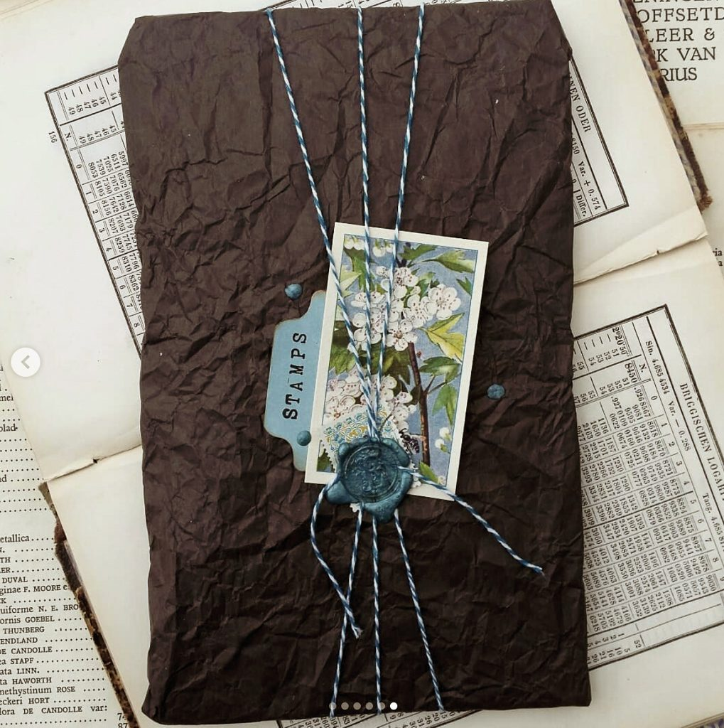 The contents are wrapped in black creche paper with a trade cards and string