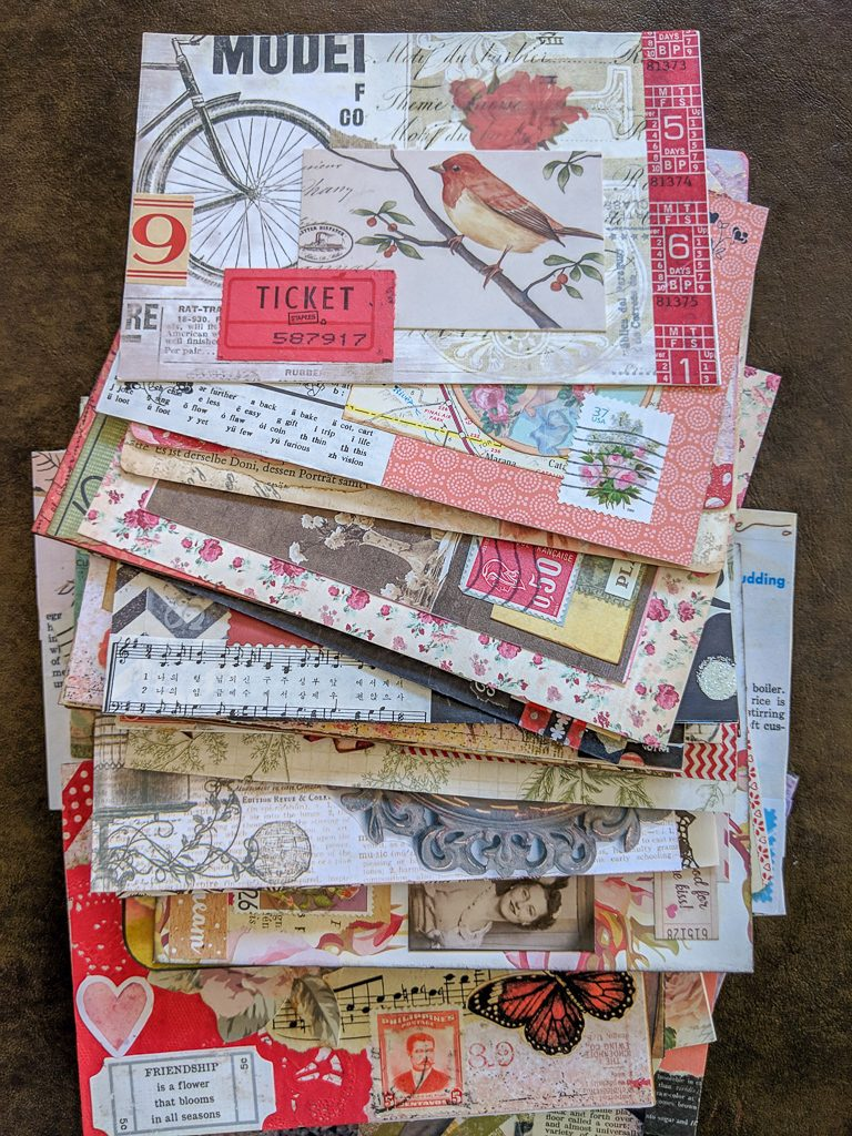 a stack of collage-art postcards, all done in a vintage style