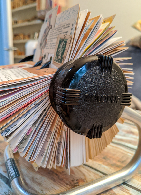 A rotary Rolodex file with collaged cards